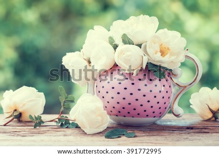 Bouquet of roses in tea kettle. Wedding or birthday still life. Retro styled. - stock photo