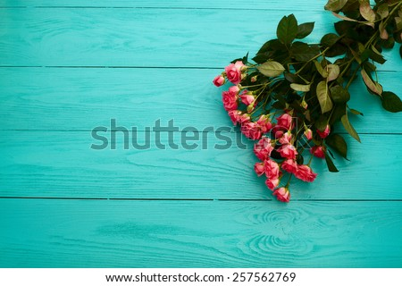 Bouquet of roses on blue wooden background - stock photo
