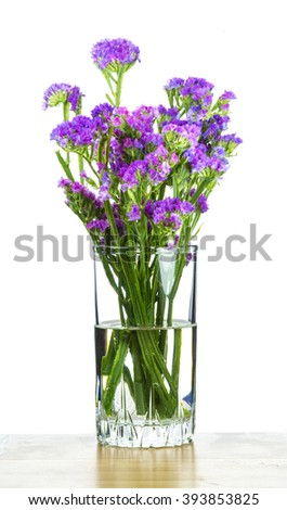 Bouquet of small violet flowers in glass. Provence mood. - stock photo