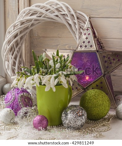 Bouquet of snowdrops and tree toy (product of mass production) in the window - stock photo