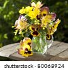 bouquet of spring flowers pansies in a jar of glass and aquilegia pink - stock photo