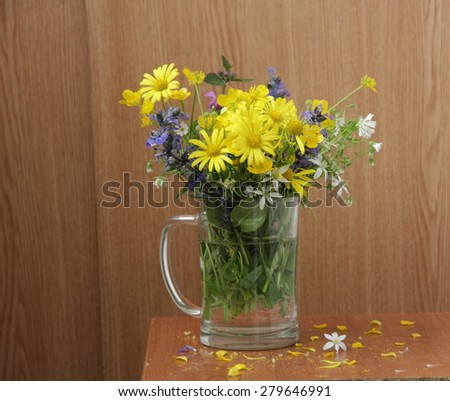 Bouquet of spring wild flowers in a transparent mug