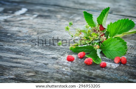 bouquet of strawberries on the board. Summer berries collected in the forest. Rural texture . Greeting Card fashion  - stock photo