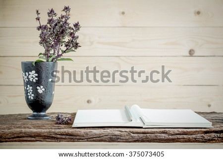 Bouquet of summer flowers in a vase and open blank notebook with space on old wooden. - stock photo