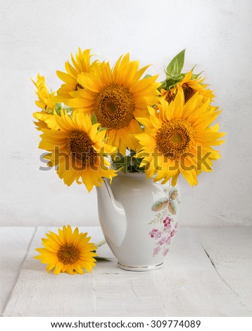 Bouquet of sunflowers in old ceramic jug against a white wooden wall. - stock photo
