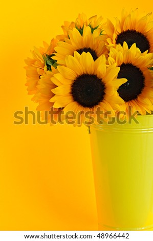 Bouquet of sunflowers in yellow metal vase - stock photo