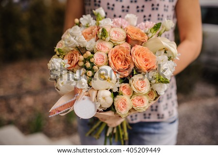 Bouquet of the different mixed  orange flowers in woman hands