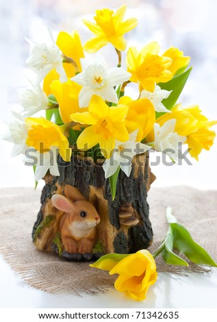 bouquet of the fresh tulips and narcissus on the table for Easter - stock photo