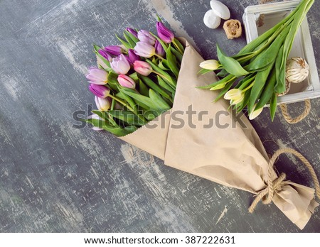 bouquet of tulips in a paper wrapper on wooden background