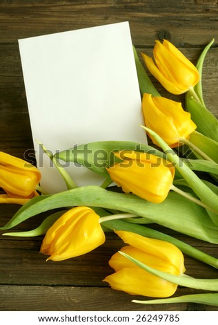 Bouquet of tulips with blank card on old wooden boards