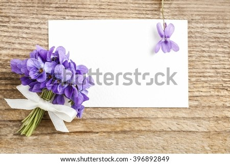 Bouquet of violet flowers (viola odorata) and paper card, copy space - stock photo