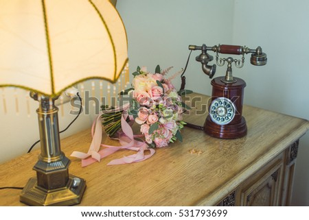Bouquet of white and pink flowers with pink ribbons near vintage phone.