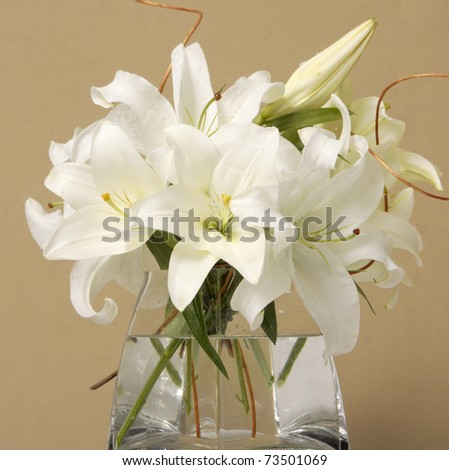 Bouquet of white Easter Lilies in a glass vase - stock photo