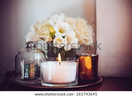 Bouquet of white flowers in a vase, candles on vintage copper tray, wedding home decor on a table - stock photo