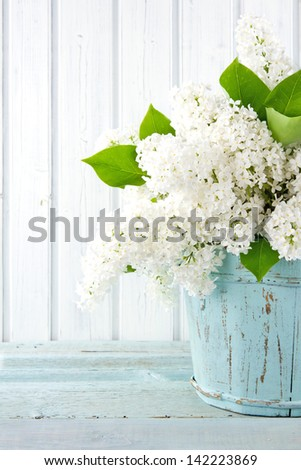 Bouquet of white lilac spring flowers in a wooden blue vase on light shabby chic background - stock photo