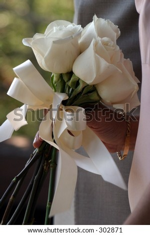 Bouquet of white roses in a woman's hand - stock photo