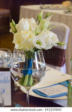 Bouquet of white roses on wedding table. - stock photo