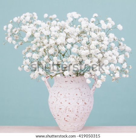Bouquet of white tiny gypsophila (baby's-breath) flowers in an antique ceramic vase - stock photo
