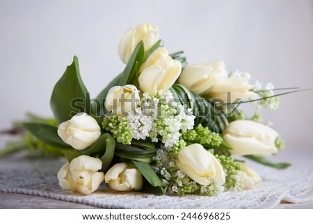 Bouquet of white tulips and white lilacs on a table in interior - stock photo