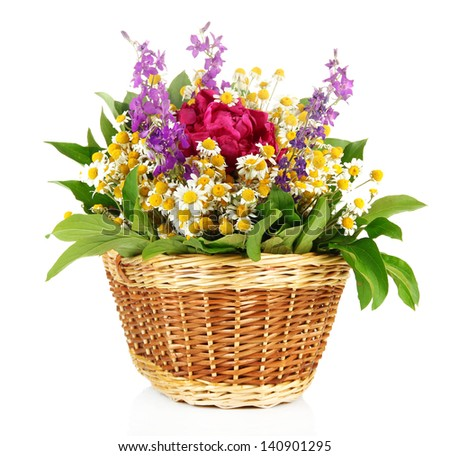 Bouquet of wild flowers in wicker basket, isolated on white