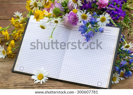 Bouquet of wildflowers and notebook with empty space for text. Good for holiday greetings - stock photo