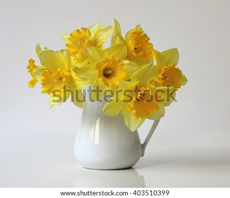 Bouquet of yellow daffodils flowers in a vase. Floral home decoration with bouquet of narcissus flowers. - stock photo
