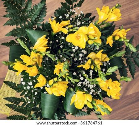 Bouquet of yellow freesia flowers. Feast theme. - stock photo
