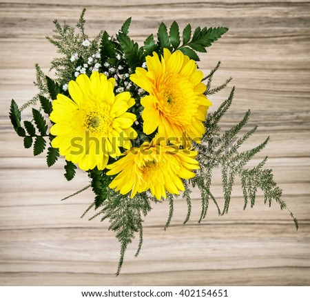 Bouquet of yellow gerbera daisies on the wooden background. Birthday gift. - stock photo