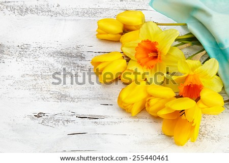 Bouquet of yellow narcissus and tulips on white wooden background - stock photo
