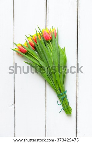 Bouquet of yellow red tulips on  white wooden background. Top view with copy space. - stock photo