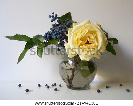 Bouquet of yellow rose and blue berries. Autumn still life on a light background. - stock photo