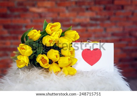 bouquet of yellow tulips and Valentines Day card - stock photo