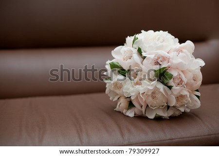 Bouquet on brown leather chair - stock photo