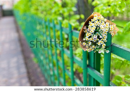 Bouquet on craft paper decoration with daisies over street and park view. Close up. - stock photo