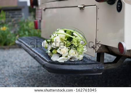 Bouquet on the rear end bottom of a white old-timer - stock photo