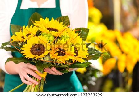 Bouquet sunflowers flower shop female florist holding - stock photo