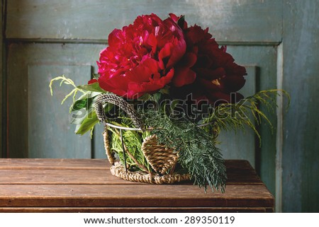 Bouquet with big burgundy peonies and green bunches of thuja in vintage vase over wooden table. Dark rustic atmosphere - stock photo