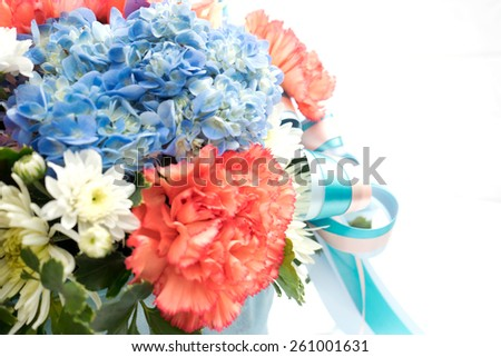Bouquet with different kind of flowers in basket isolated on white - stock photo