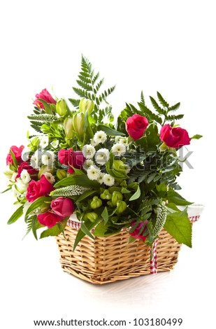 Bouquet with different kind of flowers in wooden basket over white