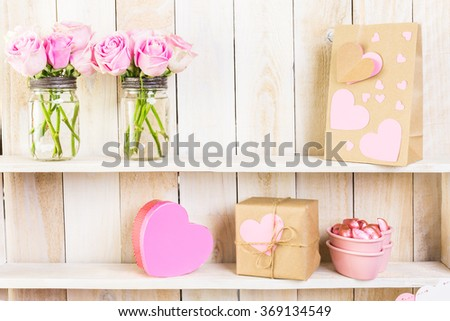 Bouquet with pink roses in mason jar on wood shelf. - stock photo