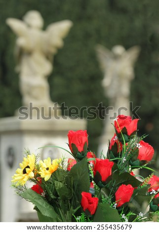 bouquet with red roses on old cemetery with angelic statues on the background, Italy - stock photo