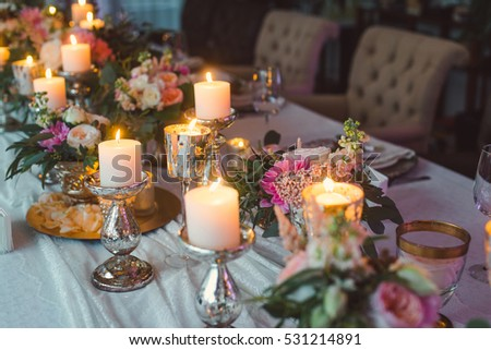 Bouquets of pink and white flowers near the candles on the table. Wedding decoration.