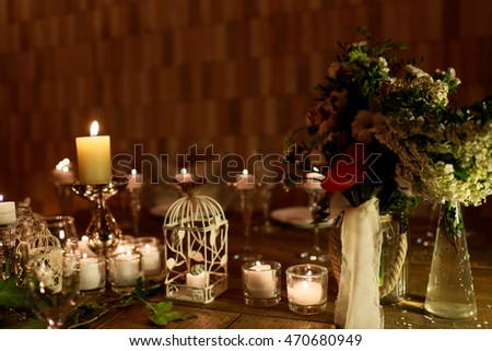 Bouquets of white flowers and greenery stand in glass vases over the candles