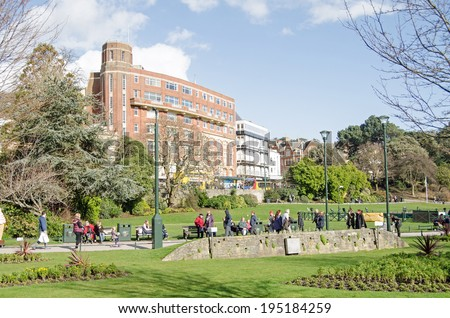BOURNEMOUTH, ENGLAND - MARCH 1, 2014: Shoppers taking a break in the Spring sunshine in Lower Gardens in Bournemouth town centre.  - stock photo