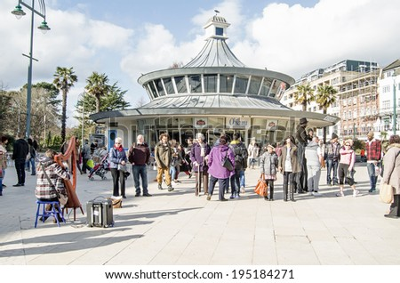 BOURNEMOUTH, ENGLAND - MARCH 1, 2014: Shoppers with a busker and man on stilts in Bournemouth Town Square, Dorset. - stock photo
