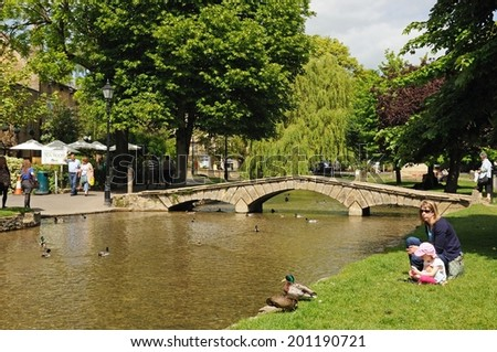 BOURTON ON THE WATER, UK - JUNE 12, 2014 - Stone footbridge across the River Windrush with tea-rooms to the rear, Bourton on the Water, Gloucestershire, England, UK, Western Europe, June 12, 2014. - stock photo