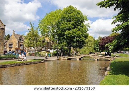 BOURTON ON THE WATER, UK - JUNE 12, 2014 - Stone footbridge across the River Windrush with tea-rooms to the rear, Bourton on the Water, Gloucestershire, England, UK, June 12, 2014. - stock photo