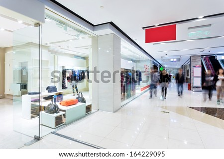 Boutique display window with mannequins in fashionable dresses - stock photo