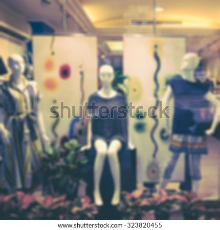 Boutique window with dressed mannequins. Boutique display window with mannequins in fashionable dresses. Retro effect. - stock photo