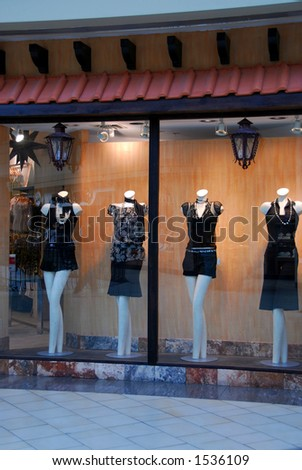 Boutique window with dressed mannequins in shopping mall - stock photo